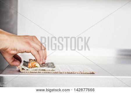 Closeup of a sushi master turning sushi rolls