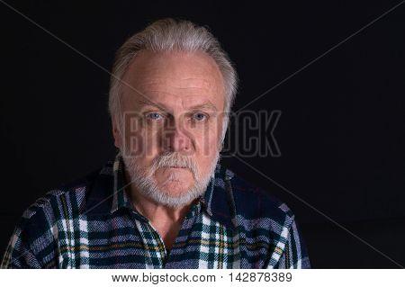 Portrait of grey-bearded Caucasian man with hard look