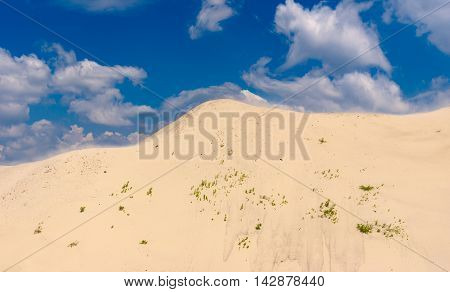 Landscape of the sandy hill and the blue sky with clouds