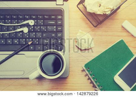 Office desk with coffee cup, notebook,headphones,  mobile smartphone and  laptop computer