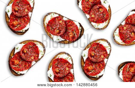 Toasted Bread withTomatoes and Cheese topped with pepper and aromatic green herbs over a white dish