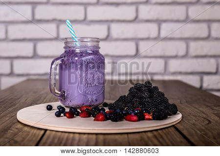Fresh homemade yogurt smoothie wild berries in a glass jar on an old vintage background, closeup. Selected focus. Harvest Concept.