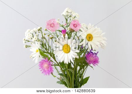 Bouquet of daisies and marigolds on a light background.