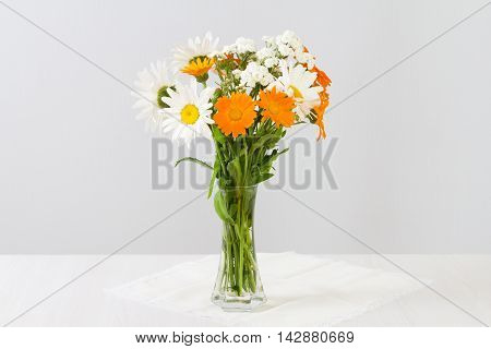 Bouquet of daisies and marigolds creeping in a vase on a white table.