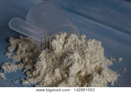 Vanilla whey protein on table with scoop