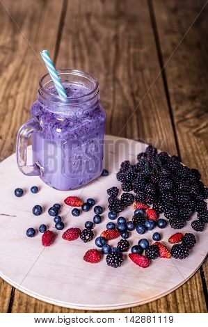Fresh homemade yogurt smoothie wild berries in a glass jar on an old vintage background, closeup, top view. Selected focus. Harvest Concept.