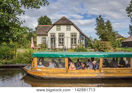 GIETHOORN, NETHERLANDS - AUGUST 9, 2016: Tourists taking a tour in the canals of Giethoorn, Holland