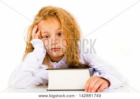 Portrait of a tired little girl with a book on a white background