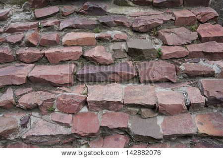 Stairs of granite rubble irregularly shaped red. Texture background