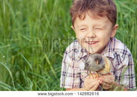 Portrait of little boy with chick outdoors at the day time.