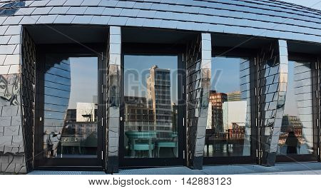 DUESSELDORF, GERMANY - FEBRUARY 27, 2016: Skyline of Duesseldorf Media Harbor reflects nicely in the glass front windows of the modern Chrome Egg building in Duesseldorf