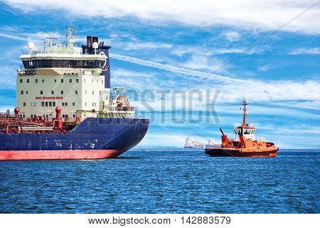 Tugboat towing a large ship on sea.
