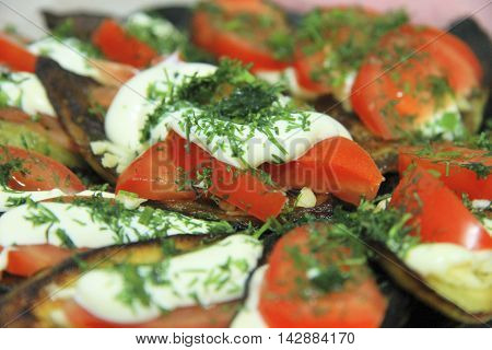 Fried eggplants and fresh tomato with souce and herbs