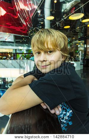 Boy Resting At A Balustrade In A Modern Shopping Center