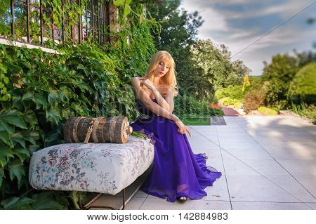 Portrait of beautiful woman dressed in evening gown. Blonde gorgeous woman in long purple luxurious dress posing in garden. Woman sitting on sofa outdoors.