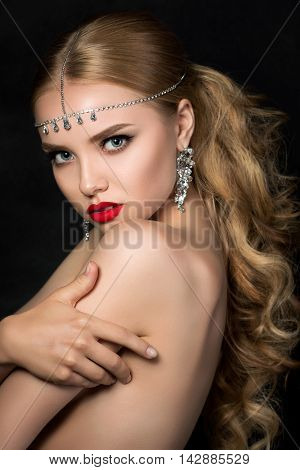Portrait of young beautiful woman with evening make up posing over dark background. Model looking at camera and touching her shoulder. Red lips and eyeliner. Classic makeup concept. Studio shot.