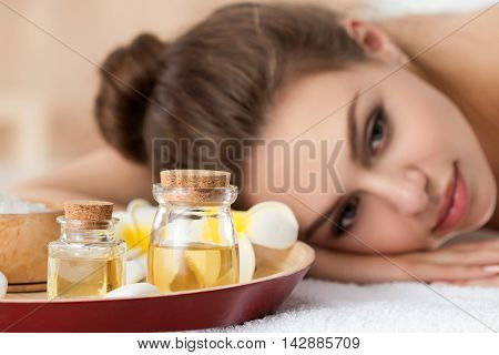 Beautiful young woman lying down at spa salon. Skin and body care healthy lifestyle relaxation massage and cosmetology concept. Focus on bottles with oils