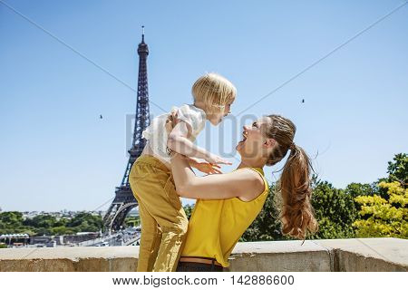 Happy Mother And Child Having Fun Time Against Eiffel Tower