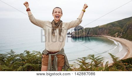 Happy Woman Hiker Rejoicing In Front Of Ocean View Landscape