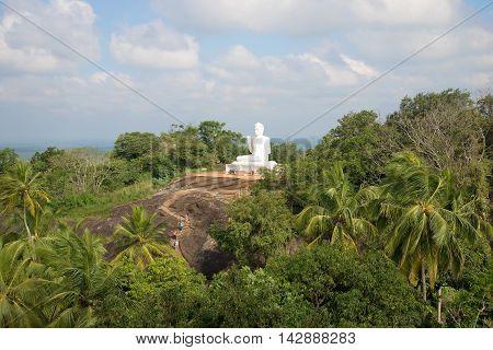View on vintage white sculpture of a sitting Buddha on the mountain Ambasthala. Mihintale, Sri Lanka