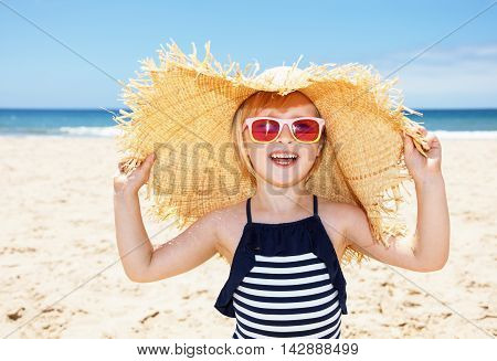 Smiling Girl In Swimsuit And Big Straw Hat On A White Beach