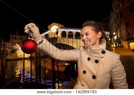 Young Woman Holding Christmas Ball Near Rialto Bridge In Venice