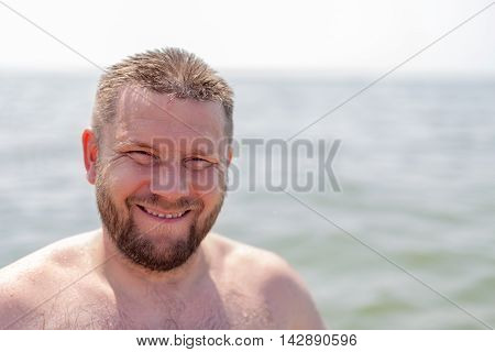 Portrait of a bearded man wet in the sea background
