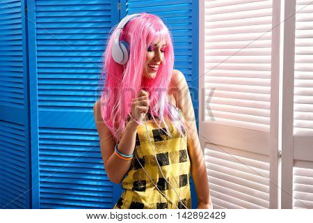 Glamour young woman with headphones on wooden screen background