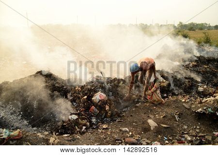 AMRAVATI, MAHARASHTRA, INDIA - APRIL 09, 2014: Unidentified people looking for something in the garbage at Big garbage land. Land and air pollution in India on April 09, 2014, Amravati, India.