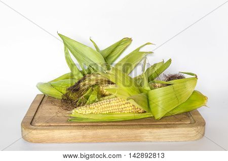 Corn cobs not yet ripe on a wooden board and white background
