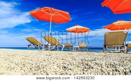 Orange beachchairs on a beach together with umbrellas