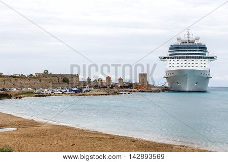 big white cruise ship in the port of the island of Rhodes Greece