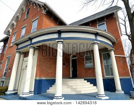 close up exterior of a red brick building and a round circular gazebo-like porch in Binghamton NY