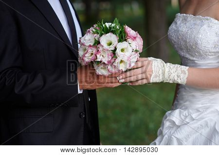 bridegroom embraces his bride, and she holds a bridal bouquet in his hands.