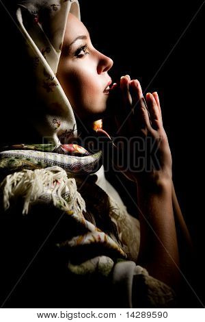 Portrait of beautiful praying girl with old russian shawl on head on black background. Retouched