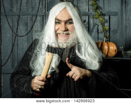 Old gray man witch in black robe with demonic grin hold hatchet near finger in wooden house