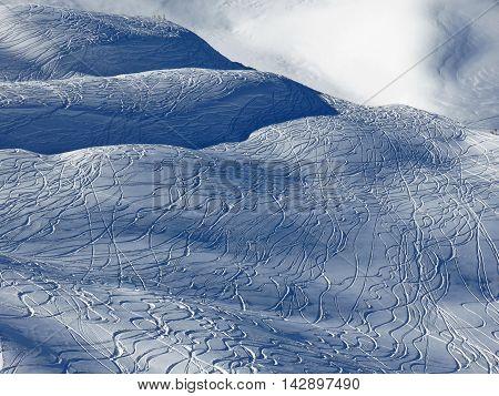 Winter scene in the Stoos ski area. Ski and snowboard tracks in powder snow.