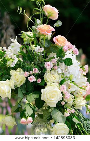 Splendid bouquet of beautiful natural fresh creamy white and pink roses with green leaves floral decor background