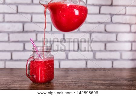 A jug pouring freshly blended red fruit smoothie in glass jar with straw. Selective focus, harvest concept.