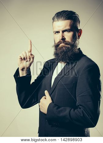 Handsome young man with long beard and moustache in black jacket with raised finger in studio on grey background