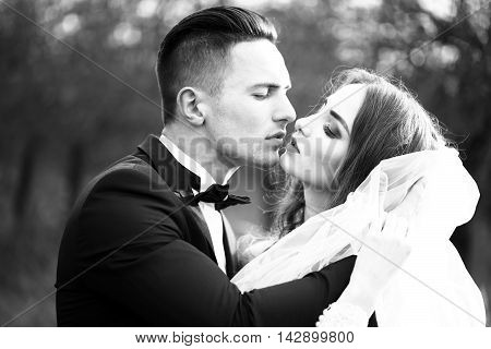 Beautiful bridal couple of young man embracing and kissing pretty woman outdoor black and white