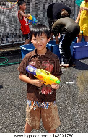 New York City - July 18 2010: Wet little boy holds his Super-Soaker water gun at the 16th annual Thingyan Burmese Water Festival