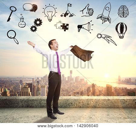 Businessperson celebrating success on concrete rooftop with abstract business icons on city background with sunlight