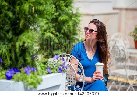 Beautiful fashion colorful shopper with bags shopping and glass of coffee in the street