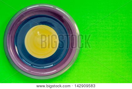 Purple blue and yellow dinner  plate on a green neon background.