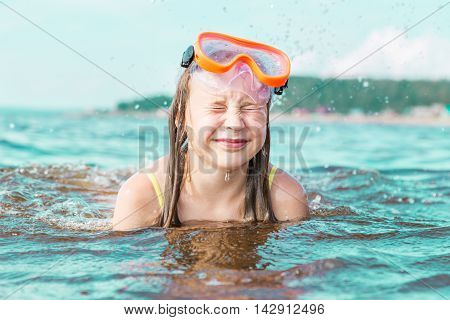 The girl squeezed her eyes shut from the sea spray swimming in the sea