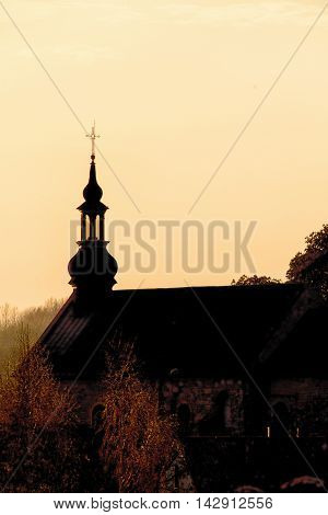 Christian religion. Tower of the small brick church at sunset or sunrise. Place of worship.