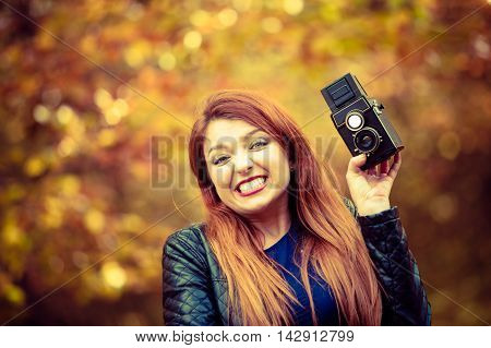 Autumn people concept. Ginger girl with analog camera. Young lady is outside during autumnal season.