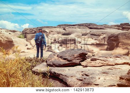 Asian woman standing outside looking at the beauty of natural stone