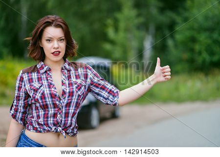 Beautiful young woman hitchhiking gesture at countryside, broken car at background.